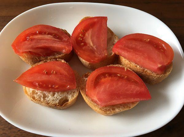ガーリックを塗ったフランスパンにトマトを載せた所